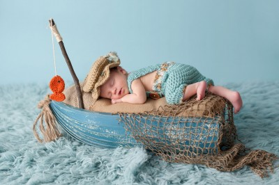 48645120 - portrait of a three week old newborn baby boy. he is sleeping in a miniature boat and wearing crocheted overalls and a fisherman's hat. shot in the studio on an aqua colored flokati rug.